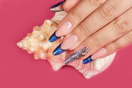 Hand with long artificial blue french manicured nails and a seashell