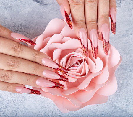 Hands with long red artificial french manicured nails and pink rose flower