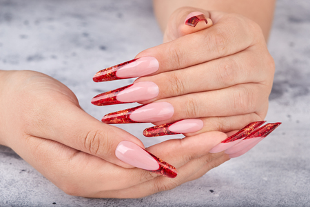 Hands with long red artificial french manicured nails