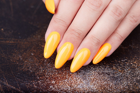 Hand with long artificial manicured nails colored with yellow nail polish Banco de Imagens