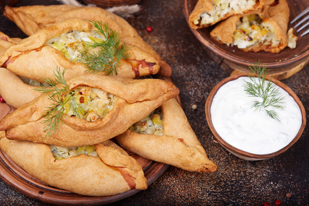 Pies with chicken meat and potatoes. Delicious small savory pirozhki served with sour cream sauce. Banco de Imagens