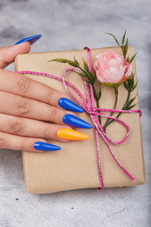 Hand with artificial manicured nails colored with blue and orange nail polish holding a gift box with bow and pink flower