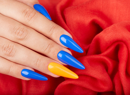 Hand with artificial manicured nails colored with blue and orange nail polish on textile background