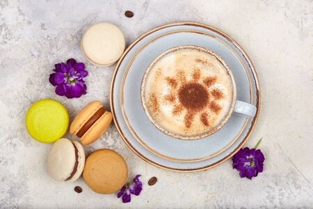 Cup of cappuccino coffee and colorful French dessert macarons
