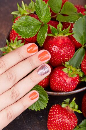 Hand with short manicured nails colored with red nail polish and strawberries