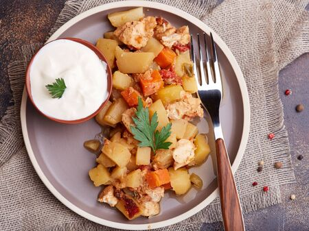 Stewed potatoes with chicken meat, carrot, tomato and sweet pepper