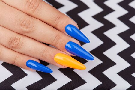 Hand with long artificial manicured nails colored with blue and orange nail polish Banco de Imagens