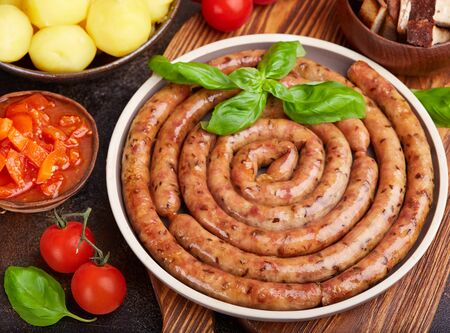Fried pork sausages served with boiled potatoes, sauce, tomatoes and basil leaf