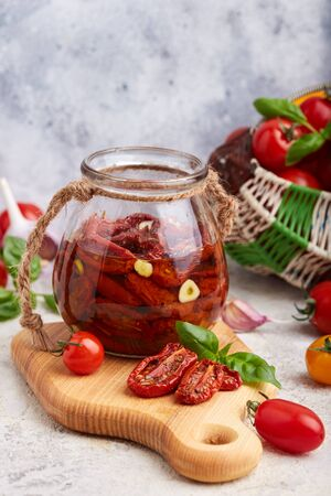 Sun dried tomatoes with herbs, garlic and olive oil in jar. Vegetarian food. Banco de Imagens