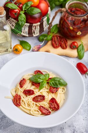 Spaghetti pasta with sun dried tomatoes and basil leaf. Vegetarian food.