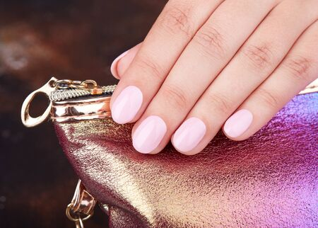 Hand mit kurzen, manikürten Nägeln, die mit rosa Nagellack gefärbt sind