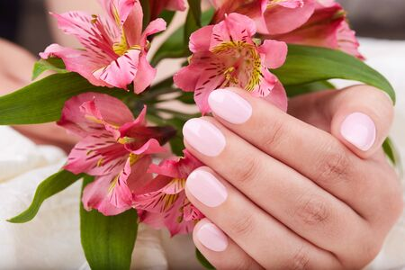 Hand with short manicured nails colored with pink nail polish and lily flowers