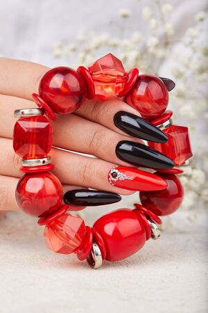 Hand with long artificial manicured nails colored with black and red nail polish holding a bracelet
