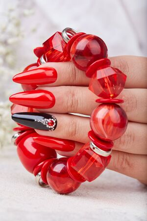 Hand with long artificial manicured nails colored with red and black nail polish holding a bracelet