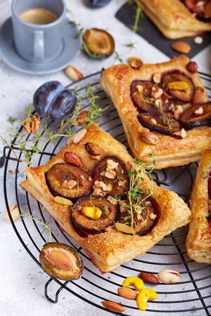 Delicious puff pastries with plums, honey, nuts, cinnamon and thyme 写真素材