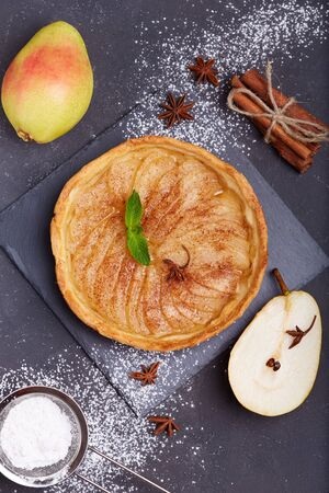 Delicious tart with pears, cinnamon and sugar powder. Open pie, sweet taste. Autumn dessert.