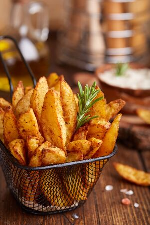 Potato wedges baked with rosemary. Delicious snack served with sauce. Fast food.