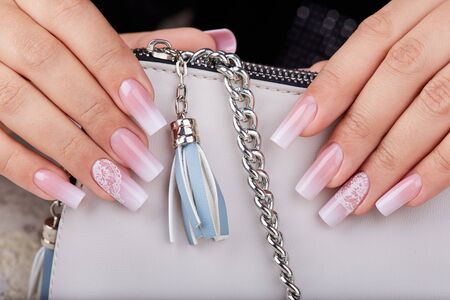 Hands with long artificial manicured nails with ombre gradient design in pink and white colors 写真素材