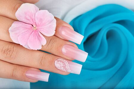 Hand with long artificial manicured nails with ombre gradient design in pink and white colors