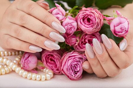 Hands with long artificial manicured nails colored with nail polish with silver glitter and pink roses