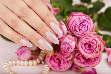 Hand with long artificial manicured nails colored with nail polish with silver glitter and pink roses