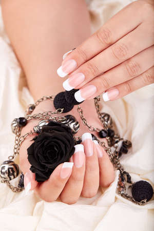 Hands with long artificial french manicured nails holding black rose flower and necklace