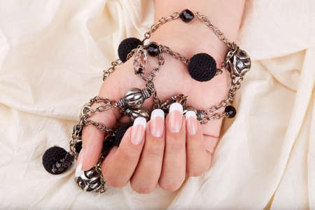 Hand with long artificial french manicured nails holding a necklace