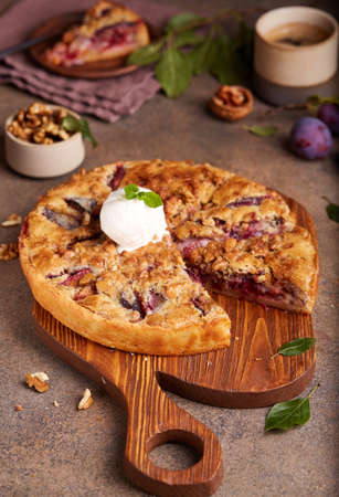 Closed pie filled with plums and walnuts. Sweet homemade dessert served with vanilla ice cream. Stockfoto