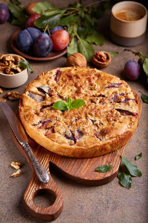Closed pie filled with plums and walnuts. Sweet homemade dessert. Stockfoto