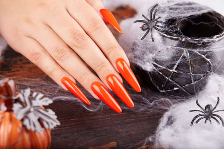 Hand with long artificial manicured nails colored with orange nail polish and Halloween decorations