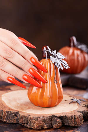 Hand with long artificial manicured nails colored with orange nail polish and pumpkin Halloween decorations Stockfoto