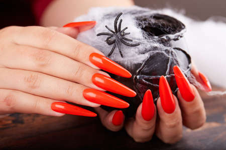 Hands with long artificial manicured nails colored with orange nail polish and Halloween decorations Stockfoto