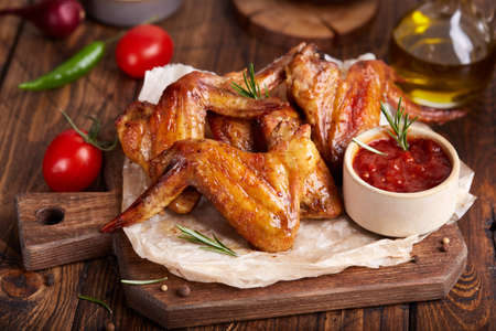 Backed Chicken wings served with rosemary and barbecue sauce. Delicious homemade appetizer.