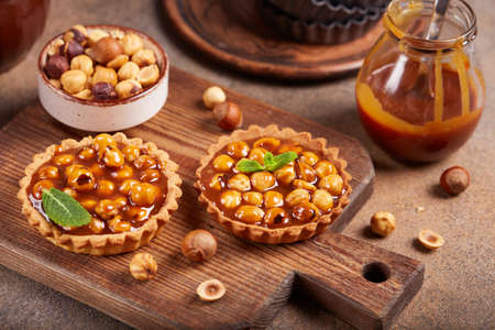 Mini tarts with hazelnuts and caramel cream filling. Sweet homemade dessert. Stockfoto