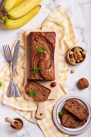 Banana bread with walnuts, hazelnuts and cinnamon. Sweet homemade dessert. Top view