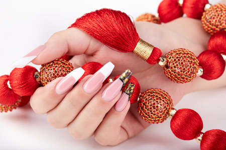 Hand with long artificial white and black french manicured nails and red necklace Stockfoto