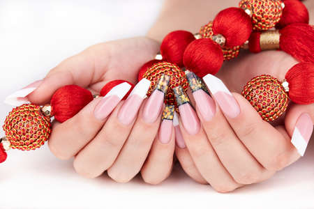Hands with long artificial white and black french manicured nails and red necklace
