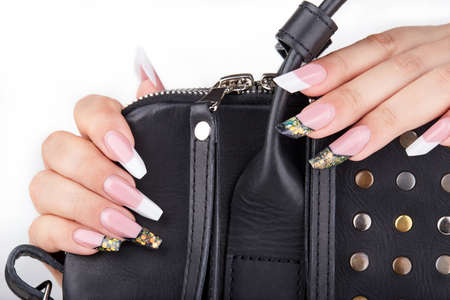 Hands with long artificial white and black french manicured nails and a handbag, white background. Fashion and stylish manicure