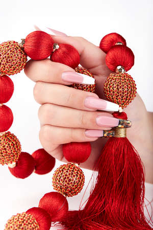 Hand with long artificial white and black french manicured nails and red necklace. Fashion and stylish manicure
