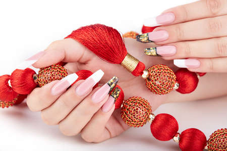 Hands with long artificial white and black french manicured nails and red necklace. Fashion and stylish manicure. White background Stockfoto