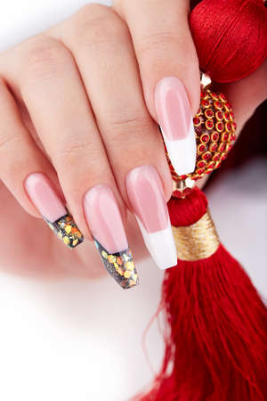 Hand with long artificial white and black french manicured nails and red necklace. Fashion and stylish manicure.