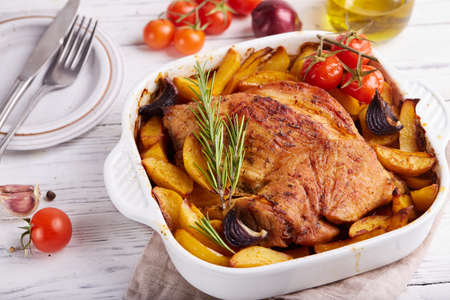 Turkey breast meat baked with potato wedges, red onion, tomatoes and rosemary. Healthy dinner for the family. Stockfoto