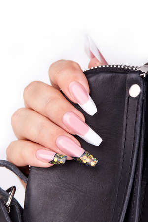 Hand with long artificial white and black french manicured nails and a handbag. White background. Fashion and stylish manicure