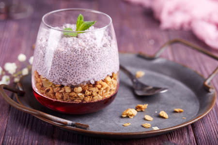Chia seeds pudding with granola muesli, and cherry jelly served as layered dessert in glass. Stockfoto