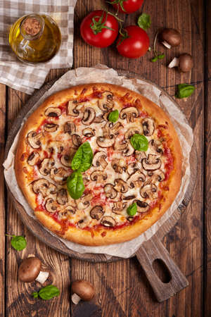 Pizza with mushrooms. American style homemade pizza with champignon mushrooms, mozzarella cheese and tomato sauce. Freshly backed and served with basil leafs. Stockfoto