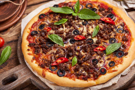 Beef barbeque Pizza with minced meat, red onion, chili pepper, black olives and mozzarella cheese. American style homemade pizza. Freshly baked and served with basil leafs.