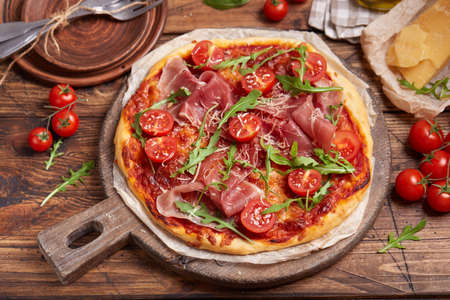 Pizza with prosciutto meat, cherry tomatoes, arugula, mozzarella and parmesan cheese. Freshly baked homemade pizza. Stockfoto