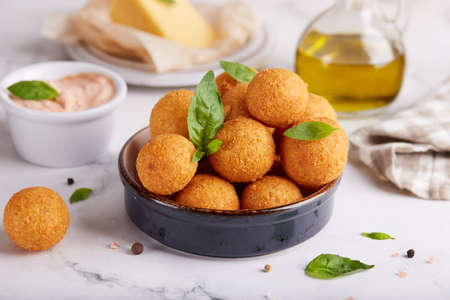 Deep fried Cheese balls. Delicious homemade appetizer. Freshly baked croquettes, served with basil leafs and sauce.