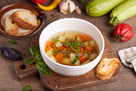 Broth with beef meat, green peas, zucchini, potato and carrot. Delicious homemade clear soup, served with basil leaves and toasts.