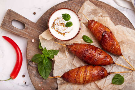 Chicken Lula kebab wrapped in slices of bacon served with yoghurt sauce with mustard. Minced meat cutlet on skewers